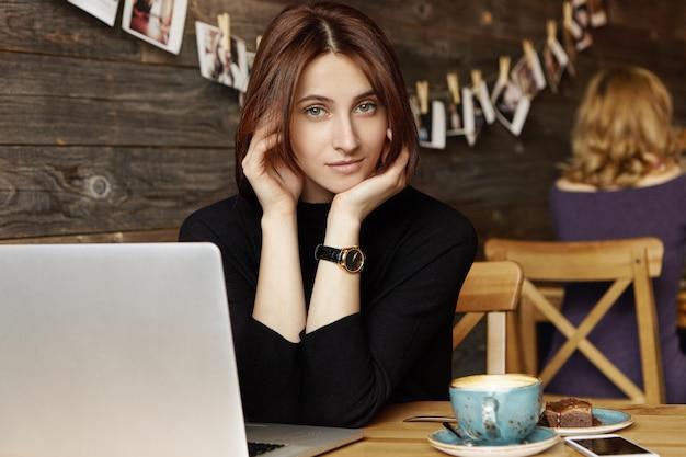 Atraente jovem colunista feminina europeia vestida com vestido preto, sentado à mesa de café com caneca, sobremesa, telefone móvel e computador portátil, trabalhando em novo artigo para a revista feminina online