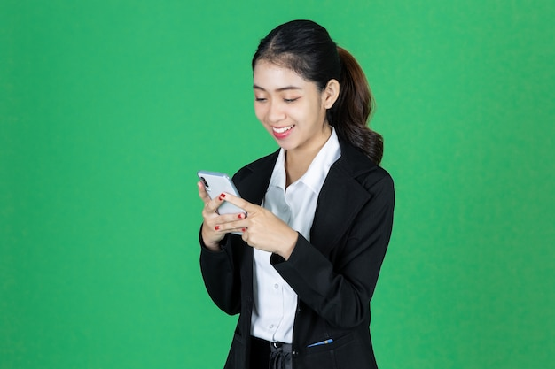 Atraente jovem empresária asiática com telefone móvel esperto nas mãos