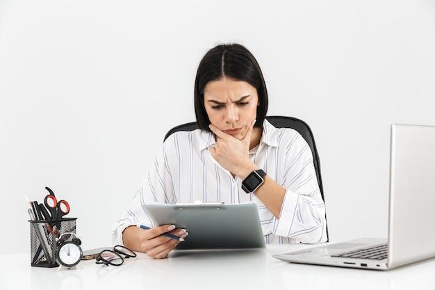 Atraente jovem empresária séria sentada na mesa isolada sobre a parede branca
