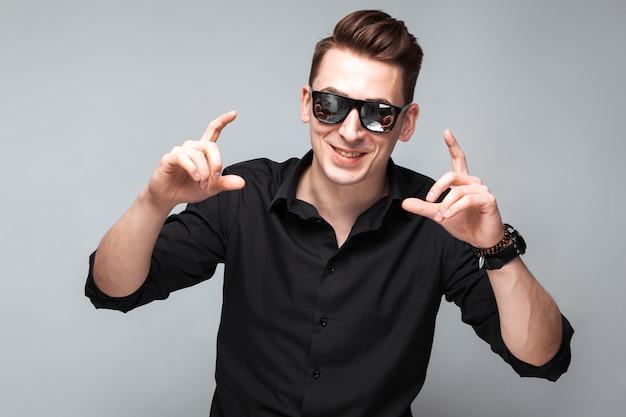 Atraente jovem empresário em relógio caro, óculos escuros e camisa preta