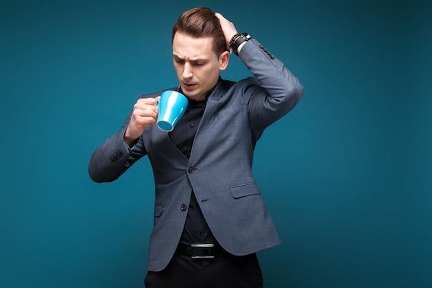 Atraente jovem empresário na jaqueta cinza e camisa preta segurar copo azul