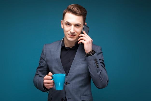 Atraente jovem empresário na jaqueta cinza e camisa preta segurar o copo azul e falar ao telefone