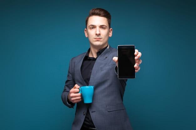 Atraente jovem empresário na jaqueta cinza e camisa preta segurar o copo azul e mostrar o telefone