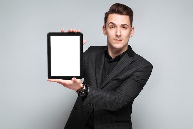 Atraente jovem empresário na jaqueta preta, relógio caro e camisa preta segurar o tablet vazio