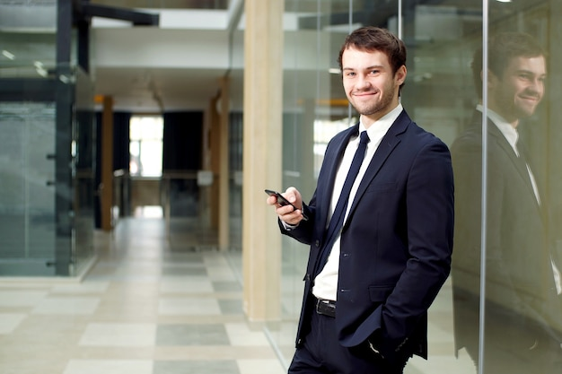 Atraente jovem empresário usa smartphone no interior do edifício de escritório moderno