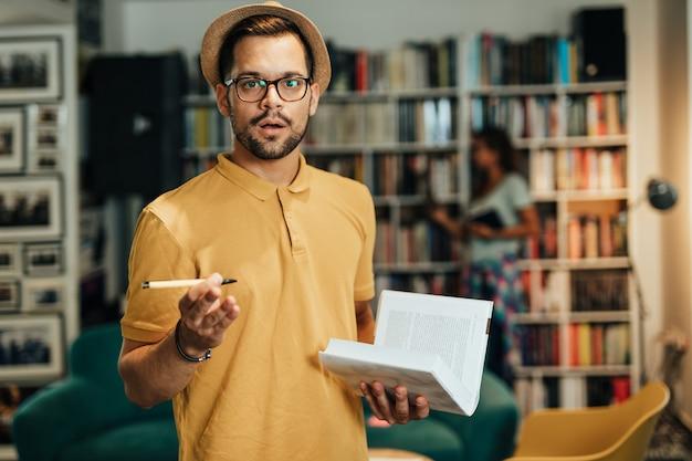 Atraente jovem estudante do sexo masculino na biblioteca da universidade.