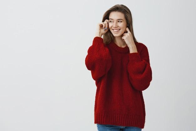 Atraente jovem estudante feminino adorando belos dias de neve, olhando pela janela na camisola solta vermelha, virando à esquerda sorrindo satisfeito e macio, tocando a pele clara macia contra