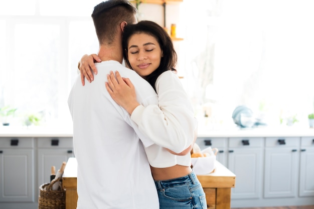 Atraente jovem étnica abraçando o namorado com os olhos fechados