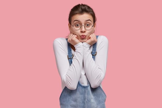 Atraente jovem europeia faz beicinho, segura o queixo com as duas mãos e olha através de óculos redondos