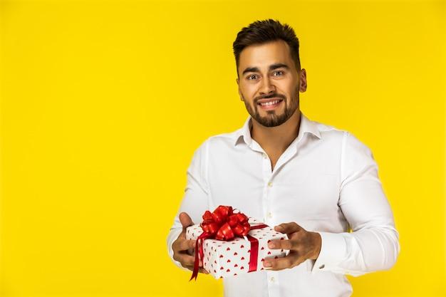 Atraente jovem europeu na camisa branca está segurando um presente
