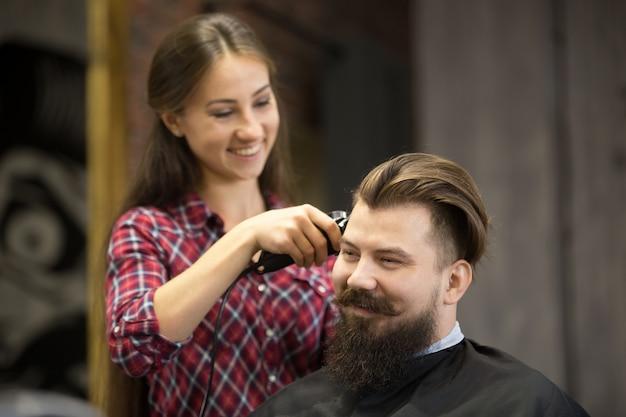 Atraente jovem feliz no salão de cabeleireiro