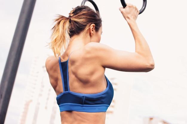 Atraente jovem forma apta na garota de desgaste do esporte puxa os anéis na área de treino de rua