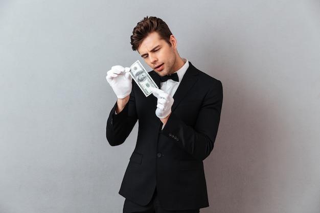 Atraente jovem garçom segurando o dinheiro.