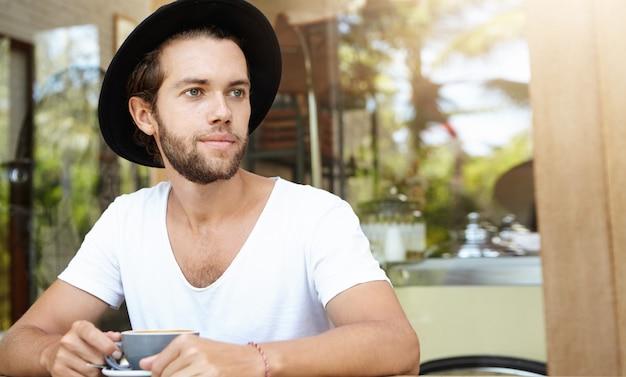 Atraente jovem homem branco com barba espessa relaxando sozinho em um restaurante na calçada, bebendo café ou chá, com olhar pensativo e sonhador