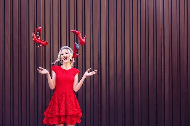 Atraente jovem loira com um vestido vermelho vomita sapatos vermelhos. o conceito de compras e vendas
