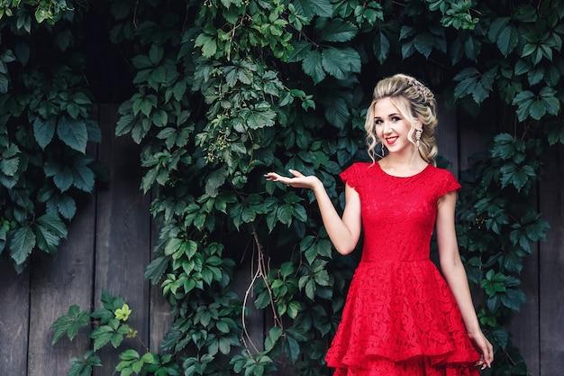 Atraente jovem loira com vestido vermelho tem espaço de cópia na palma da mão contra o pano de fundo de vinhedo selvagem.