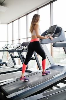 Atraente jovem modelo de fitness corre em uma esteira, está envolvido em um clube de esporte fitness