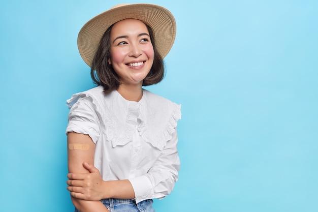 Atraente jovem morena asiática com braço vacinado usa chapéu estiloso, blusa branca desenrola manga mostra ombro nu com esparadrapo isolado sobre parede azul