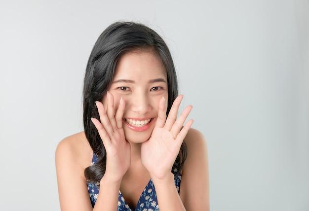 Atraente jovem mulher asiática anunciando com as mãos na boca e contando um segredo