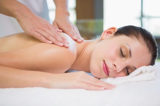 Atraente jovem recebendo massagem no ombro no centro de spa
