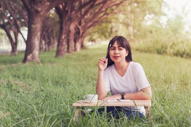 Atraente jovem sentado escrever um diário e beber café na grama