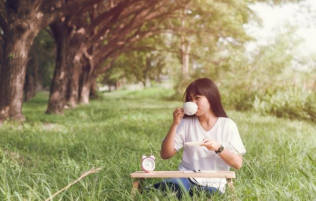 Atraente jovem sentado escrever um diário e beber café