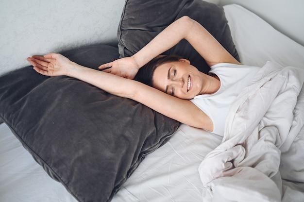 Atraente jovem sorridente, estendendo-se na cama, acordando sozinho feliz conceito, acordado após um sono saudável na confortável cama confortável e colchão desfrutar de bom dia