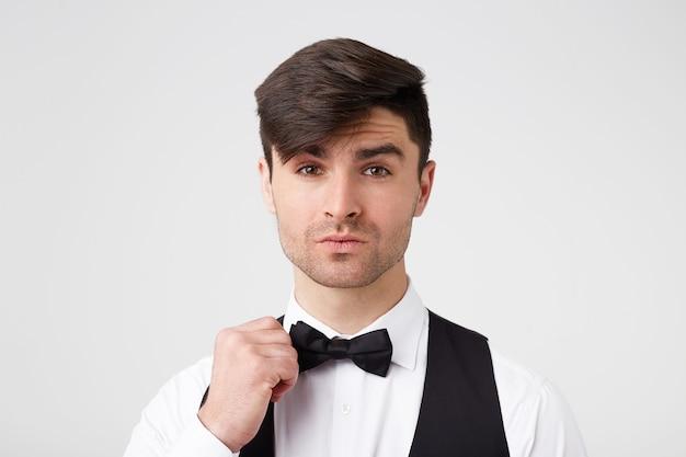 Atraente lindo rapaz de cabelos escuros bem vestido corrige a gravata borboleta, parece encantador