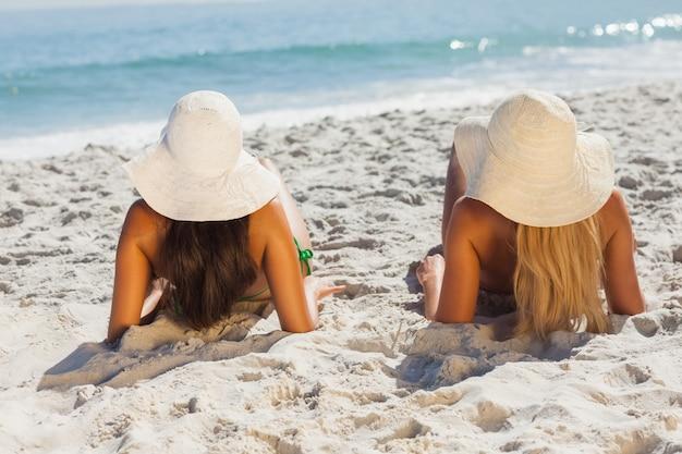 Atraente loira e morena em biquínis deitada na areia