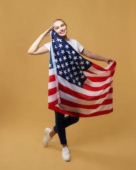 Atraente loira posa com orgulho com uma bandeira americana. sessão de fotos no estúdio em um fundo amarelo.