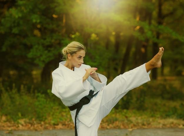 Atraente lutadora master usando quimono branco e faixa preta chutando ao ar livre
