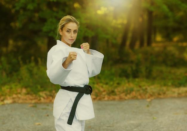 Atraente lutadora mestre em um quimono branco e faixa preta em posição de combate ao ar livre
