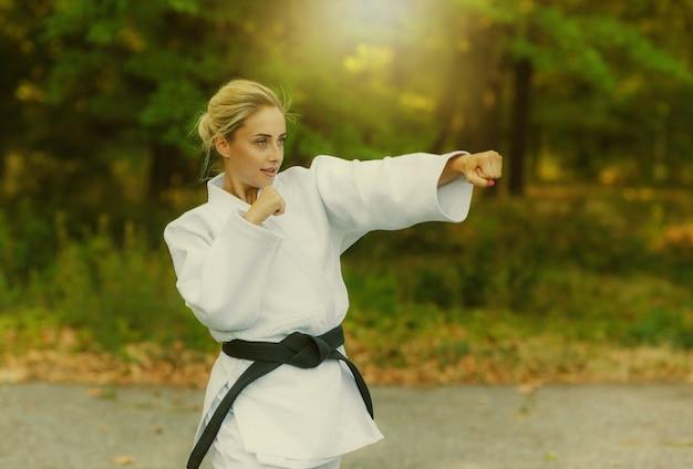 Atraente lutadora mestre em um quimono branco e faixa preta esfaqueia com a mão ao ar livre