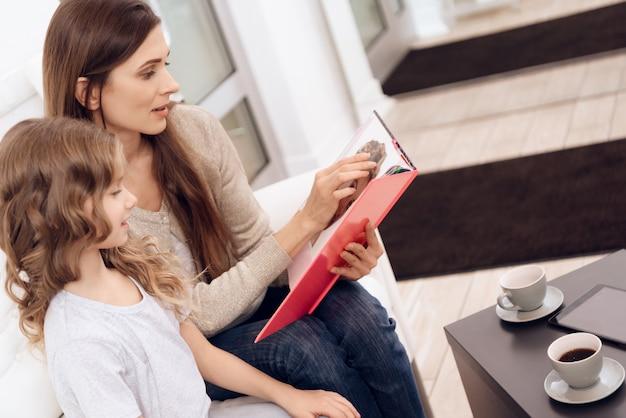 Atraente mãe com filha escolher o estilo de cortes de cabelo.
