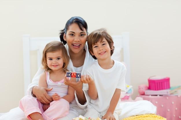 Atraente mãe e seus filhos brincando com blocos de letras