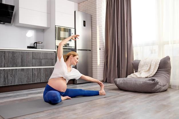 Atraente mamãe esportiva esticando as pernas durante o treino em casa