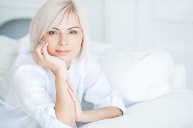 Atraente meados retrato de mulher adulta. fêmea dentro retrato closeup. retrato louro da beleza da mulher em casa.