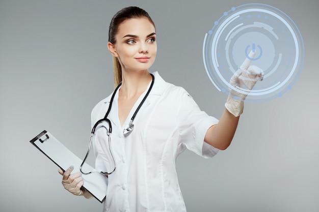 Atraente médica com cabelo castanho e nude compõe vestindo túnica médica branca e estetoscópios mostrando com a mão no fundo cinza, o conceito de cuidados de saúde e farmacologia, garota em uniforme branco.
