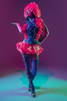 Atraente. modelo moreno havaiano na parede roxa em luz de néon. mulheres bonitas em roupas tradicionais, sorrindo, dançando e se divertindo. férias brilhantes, cores de celebração, festival.