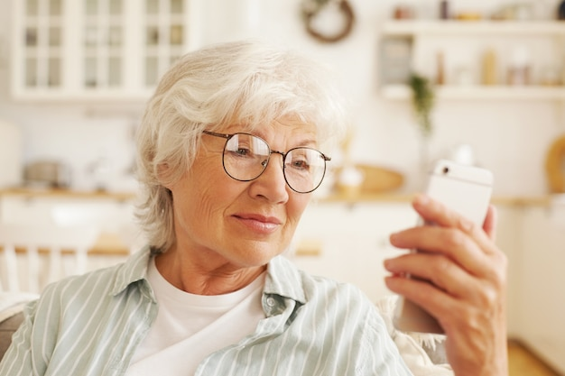 Atraente moderno sênior feminino pensionista em copos redondos, sentado no sofá, segurando o telefone celular genérico, lendo sms. mulher aposentada de cabelos grisalhos navegando na internet usando uma conexão sem fio de 4 g