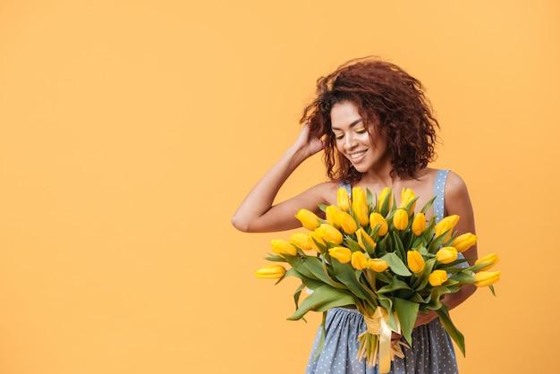 Atraente mulher africana segurando o buquê de flores