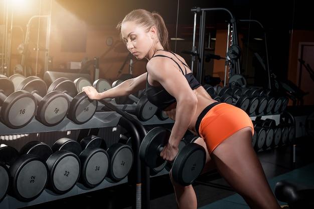 Atraente mulher apta trabalha com halteres no ginásio