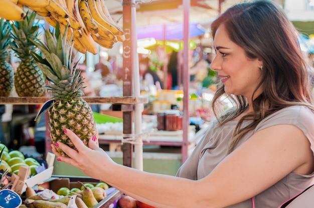 Atraente mulher comprando no mercado verde. closeup portrait jovem mulher bonita pegando, escolhendo frutas, abacaxis. expressão de expressão positiva emoção que sente um estilo de vida saudável