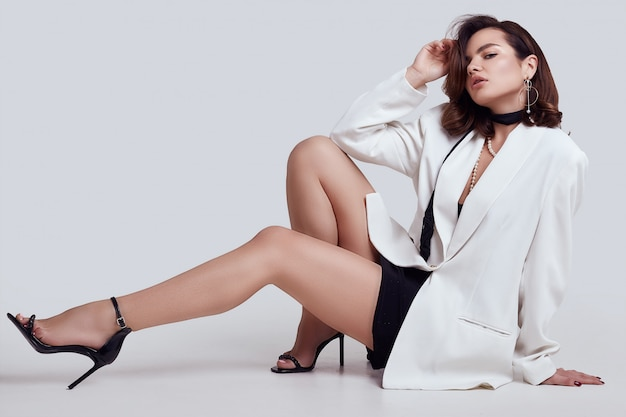 Atraente mulher elegante com cabelos escuros na moda terno branco