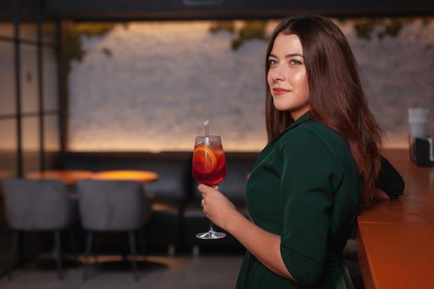 Atraente mulher elegante, tomar uma bebida no bar à noite
