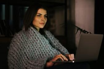 Atraente, mulher, em, cobertor, browsing, laptop