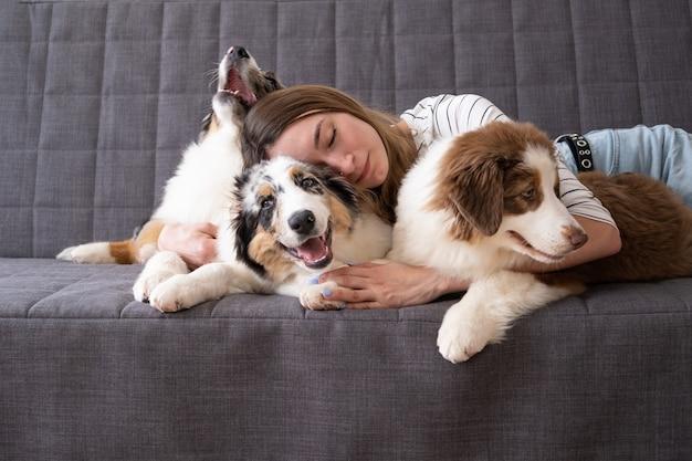 Atraente mulher feliz abraço deitado sobre três cachorrinho de cachorro bonito pastor australiano azul merle vermelho três cores. deitada no sofá. amor e amizade entre humanos e animais.