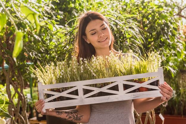 Atraente, mulher feliz, segurando, prateleira madeira, com, plantas