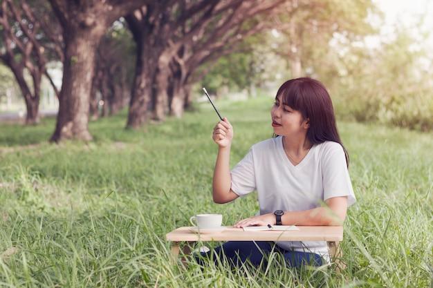 Atraente, mulher jovem, sentando, escreva, idéia