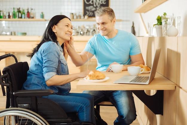 Atraente mulher morena sorridente com deficiência e um homem loiro feliz e bonito sentado à mesa em um café, ouvindo música e tomando um café